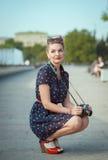 Den härliga unga kvinnan i femtiotal utformar den hållande retro kameran arkivfoton