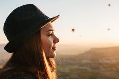 Den härliga unga kvinnan i hatt ser joyfully härligt landskap under flyg på ballongen för varm luft mot bakgrund arkivfoton