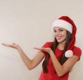 Den härliga unga kvinnan i jultomtenhatt annonserar och visar ett ampty p arkivfoton