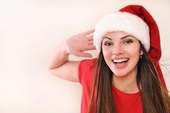 Den härliga unga kvinnan i jultomtenhatten som upphetsar om jul, semestrar royaltyfria foton