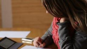 Den härliga unga kvinnan i kontoret skriver med pennan stock video