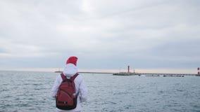 Den härliga unga kvinnan i omslag med ryggsäcken går på pir på hamnen Den attraktiva kvinnliga turisten besöker port arkivfilmer