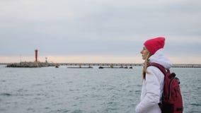 Den härliga unga kvinnan i omslag med ryggsäcken går på pir på hamnen Den attraktiva kvinnliga turisten besöker port stock video