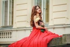 Den härliga unga kvinnan i röd klänning rymmer blomman royaltyfri bild