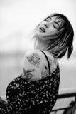 Den härliga unga kvinnan i regnet med en tatuering på hennes händer som, är sinnliga och, stillar, vått hår svart white Royaltyfri Bild