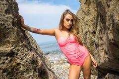 Den härliga unga kvinnan i rosa baddräkt stod mellan rocen Royaltyfri Foto
