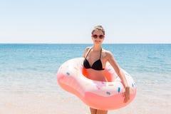 Den härliga unga kvinnan i simbassäng simmar på den uppblåsbara cirkelmunken och har gyckel med exponeringsglas av coctailen på s arkivbild