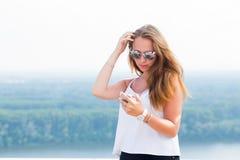 Den härliga unga kvinnan i solglasögon använder smartphonen i natur, parkerar, berg royaltyfri foto