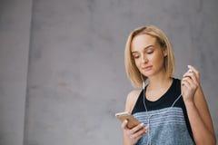 Den härliga unga kvinnan i sportar bär, och hörlurar lyssnar till musik genom att använda en smartphone royaltyfri bild