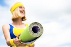 Den härliga unga kvinnan i sportar bär rymmer en yoga matt Mode sport, sunt livsstilbegrepp sportig flicka royaltyfria foton