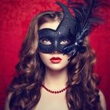 Den härliga unga kvinnan i svart mystiskt venetian maskerar Royaltyfri Fotografi