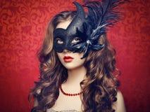 Den härliga unga kvinnan i svart mystiskt venetian maskerar royaltyfria bilder
