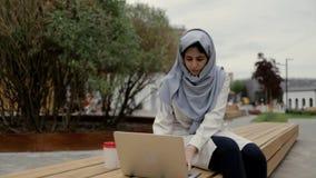 Den härliga unga kvinnan i traditionella muslim beklär maskinskrivning på bärbara datorn utanför stock video