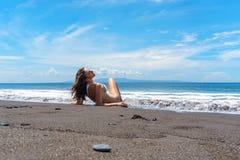 Den härliga unga kvinnan i den vita bikinin ligger på henne baksida på havstranden med svart sand, azurt vatten, och blå himmel p arkivfoto