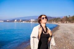 Den härliga unga kvinnan kopplar av på stranden i vinter Royaltyfri Foto