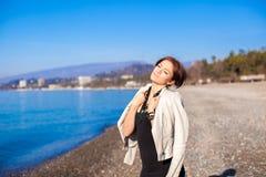 Den härliga unga kvinnan kopplar av på stranden i vinter Royaltyfri Bild