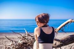 Den härliga unga kvinnan kopplar av på stranden i vinter Royaltyfria Bilder