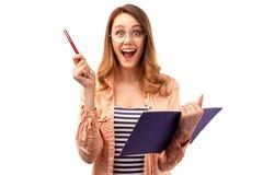 Den härliga unga kvinnan med glat uttryck bär blyertspennan, och notepaden, öppnar munnen brett, gör anmärkningar i anteckningsbo royaltyfri bild