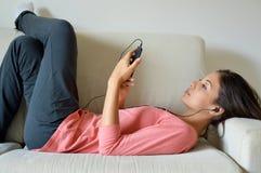 Den härliga unga kvinnan med hörlurar som kopplar av på soffan, lyssnar kyler hon till musik genom att använda en smart telefon,  royaltyfri fotografi