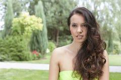 Den härliga unga kvinnan med långt krabbt hår parkerar in arkivfoto