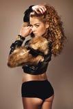 Den attraktiva unga kvinnan som poserar i innegrej, pälsfodrar. Royaltyfria Bilder