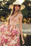 Den härliga unga kvinnan med långt mörkt hår bär den eleganta klänningen och hatten Arkivfoto