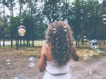 Den härliga unga kvinnan med lockigt hår som blåser bubblor parkerar in royaltyfria foton