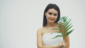 Den härliga unga kvinnan med perfekt hud och naturliga utgör att posera framdelen av tropisk grön sidabakgrund för växten med stock video