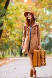 Den härliga unga kvinnan med resväskan på den underbara hösten parkerar bakgrund royaltyfri bild