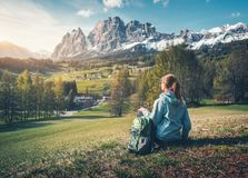 Den härliga unga kvinnan med ryggsäcken sitter på kullen royaltyfria foton