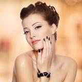 Den härliga unga kvinnan med svart spikar arkivfoton