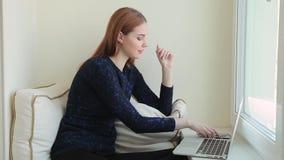 Den härliga unga kvinnan meddelar i sociala nätverk i en bärbar dator, medan sitter på fönsterbrädan hemma lager videofilmer