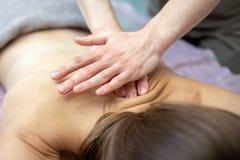 Den härliga unga kvinnan mottar en massage på en massagesalong royaltyfri fotografi