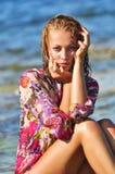 Den härliga unga kvinnan på en strand i våta dres Arkivbilder