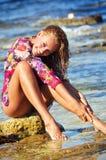 Den härliga unga kvinnan på en strand i våta dres Royaltyfri Foto