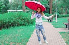 Den härliga unga kvinnan på naturen parkerar paraplyet royaltyfria bilder