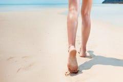 Den härliga unga kvinnan promenerar en kust Arkivfoto