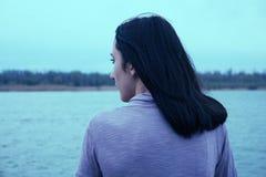 Den härliga unga kvinnan ser sikt över floden Den attraktiva kvinnan tycker om bakre sikt för sommar nShe beundrar Fotografering för Bildbyråer