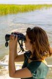 Den härliga unga kvinnan ser till och med kikare från däcket av fartyget Arkivfoton