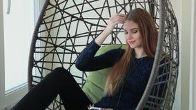 Den härliga unga kvinnan sitter i en hängestol med telefonen och lyssnar till musik arkivfilmer