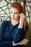 Den härliga unga kvinnan sitter i en hängestol i rummet Royaltyfria Bilder