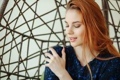 Den härliga unga kvinnan sitter i en hängestol i rummet Arkivfoton