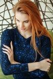 Den härliga unga kvinnan sitter i en hängestol i rummet Royaltyfria Foton