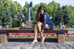 Den härliga unga kvinnan sitter på en bänk Royaltyfria Foton