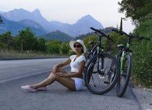 den härliga unga kvinnan sitter på kanten av en väg Arkivfoto