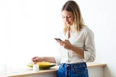 Den härliga unga kvinnan som äter yoghurt och, överför ett meddelande med hennes smartphone, medan äta yoghurt hemma royaltyfria bilder