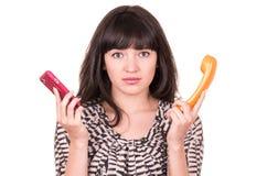 Den härliga unga kvinnan som använder den retro apelsinen, och mobiltelefonen ringer arkivbilder