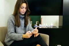 Den härliga unga kvinnan som använder hennes mobiltelefon på kafét, shoppar Arkivfoto