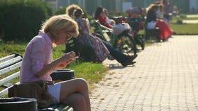 Den härliga unga kvinnan som använder den smarta telefonen på bänk parkerar in och att knacka lätt på pekskärmen lager videofilmer