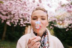 Den härliga unga kvinnan som blåser bubblor på, parkerar royaltyfria bilder